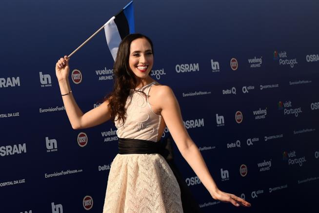 Elina Nechayeva, vestita di bianco, sul blu carpet, mentre sorride e tiene la bandiera dell'Estonia
