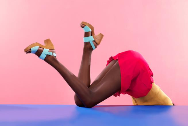 Ragazza con gambe in alto che mostra le scarpe
