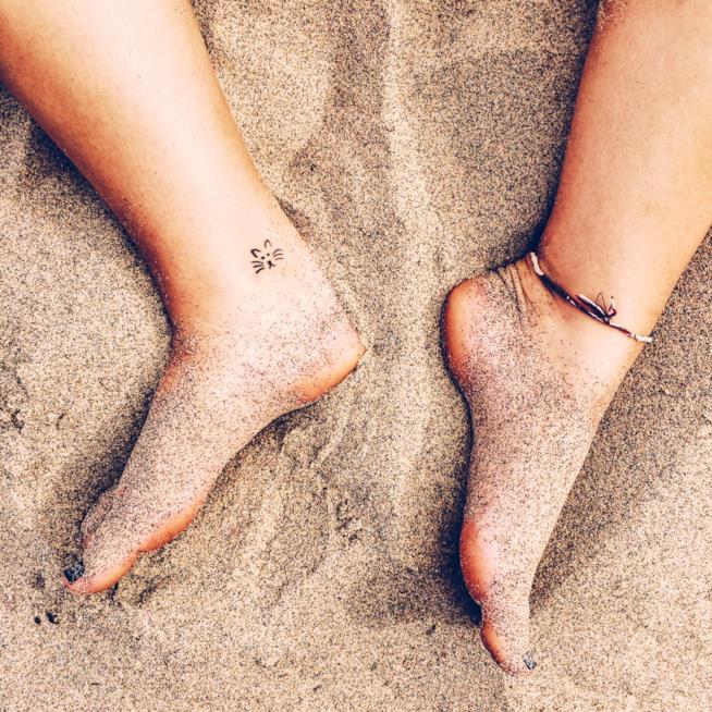 Tatuaggio felino sulla caviglia di una ragazza al mare
