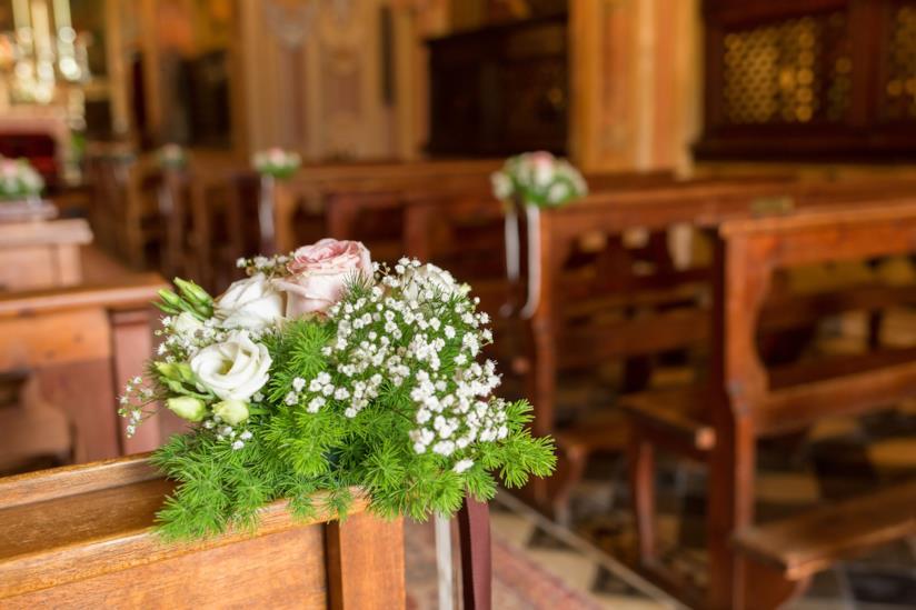 Rose e verde su una panca in chiesa per un matrimonio
