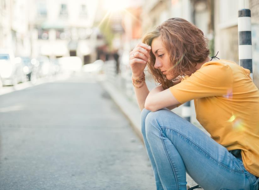 Ragazza da sola seduta sul marciapiede