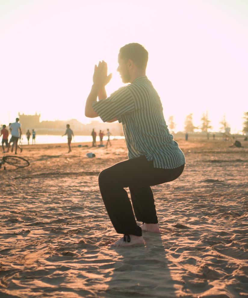 Uomo che fa squat in spiaggia