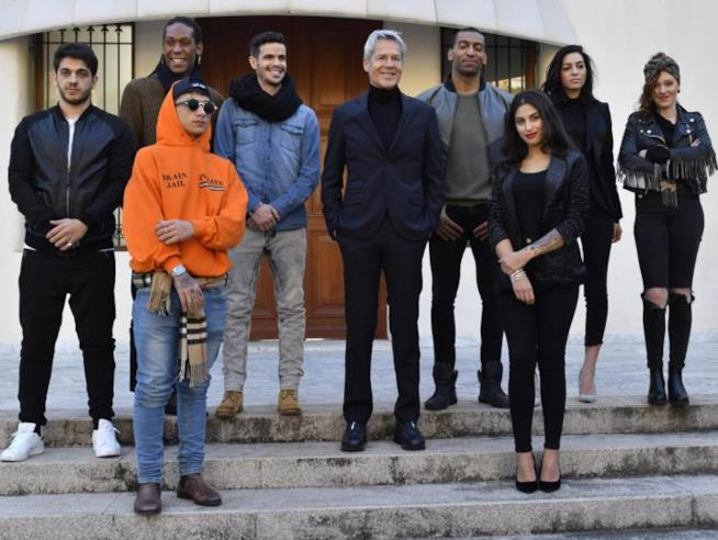 Claudio Baglioni sorridente in mezzo agli otto concorrenti delle Nuove Proposte di Sanremo