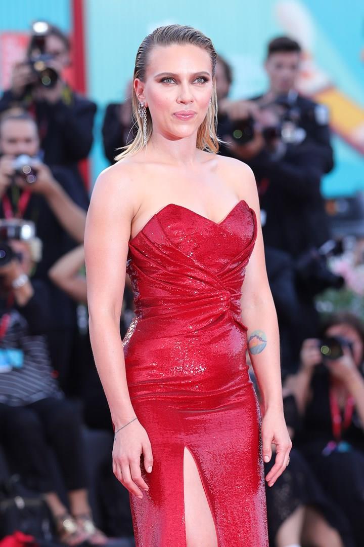 Scarlett Johansson, in piedi, con un abito rosso, davanti ai fotografi