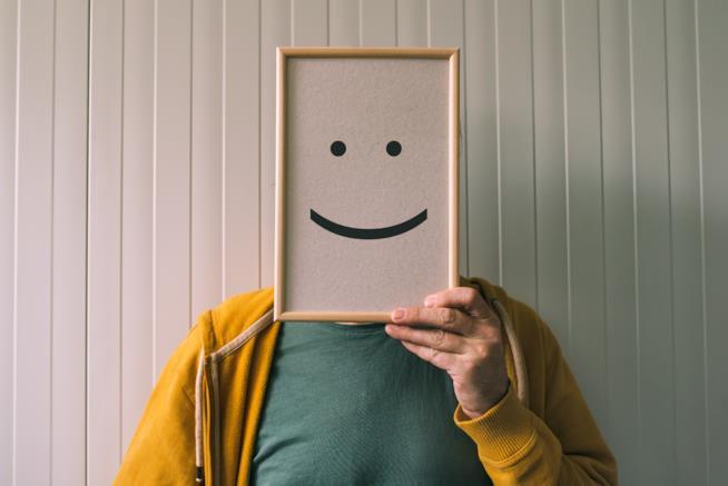 Uomo una maschera con il sorriso disegnato sopra