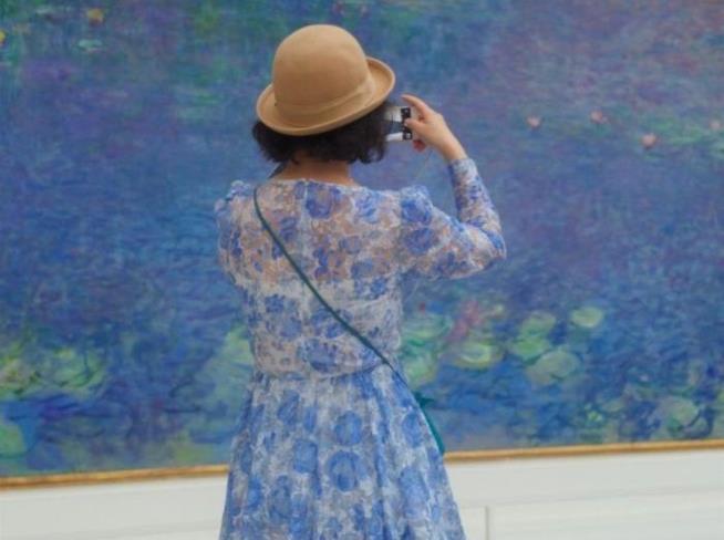 Una donna fotografa un quadro di Monet