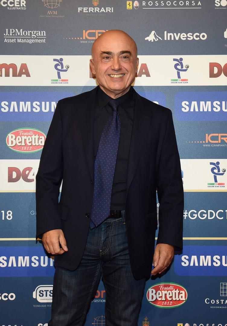 Paolo Cevoli, in nero, in piedi, sorride