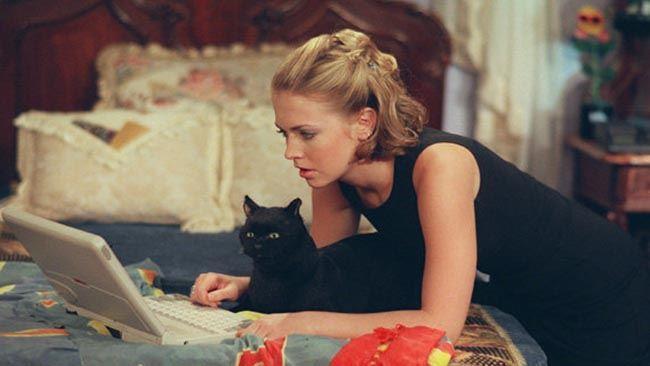Salem e Sabrina sul letto in una scena della serie Sabrina vita da strega