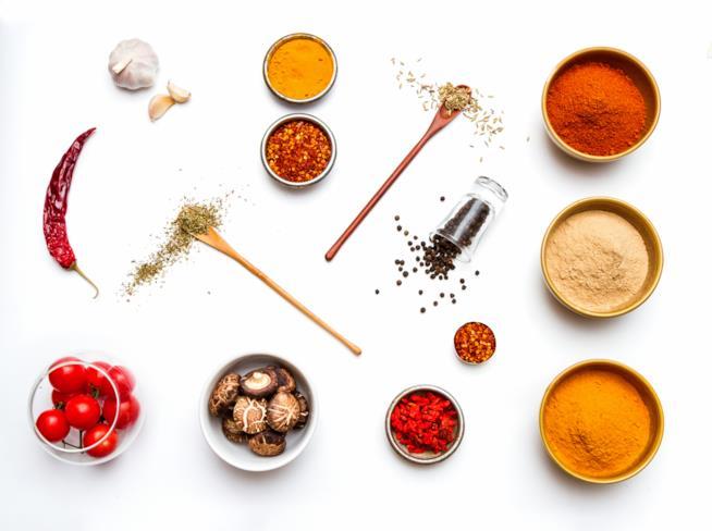 visione dall'altro di ciotole di spezie e altri ingredienti tra colori e forme molteplici