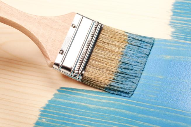 Pennello con smalto di colore azzurro per ridipingere i mobili del bagno