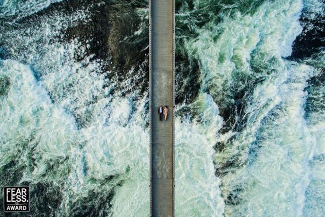 una coppia su un ponte sospeso sul mare in tempesta