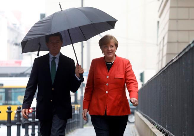 Angela Merkel e Joachim Sauer camminano sotto la pioggia insieme