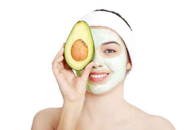 primo piano del viso di una ragazza con una maschera di bellezza all'avocado mentre tiene in mano metà del frutto