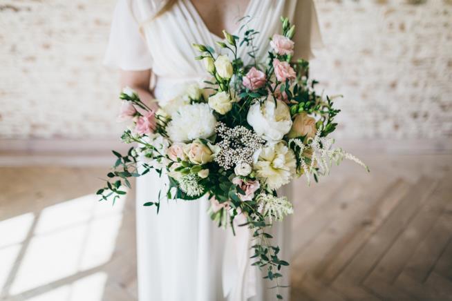 Sposa in piedi con bouquet