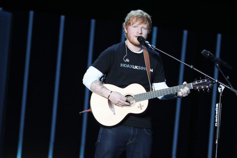 Ed Sheeran in piedi, con la chitarra in mano, canta al microfono