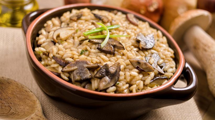 Tegame in primo piano con riso, funghi porcini e qualche filo di erba cipollina.