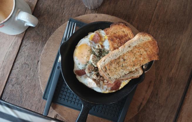 Uovo e bacon cotti nella padella in ghisa
