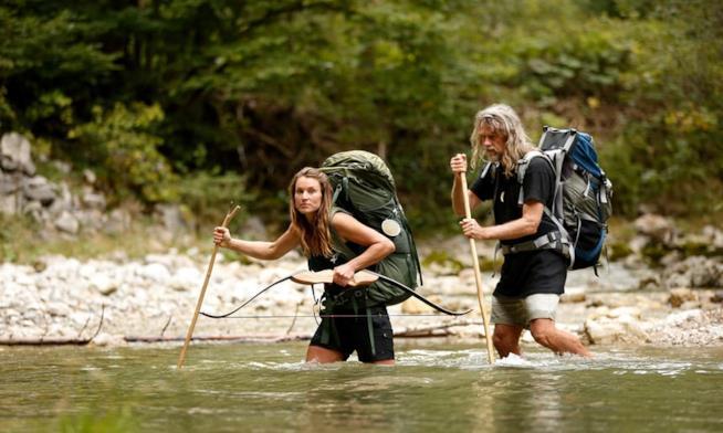 Un uomo ed una donna guadano un fiume