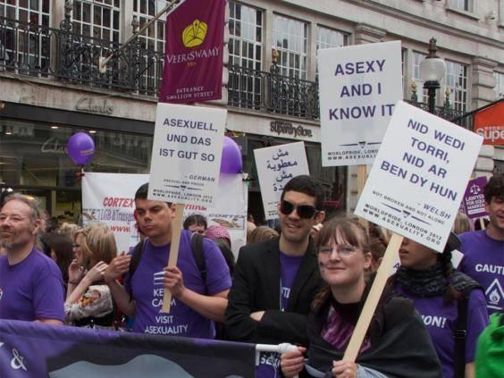 manifestanti con cartelli e tshirt viola in supporto dell'asessualità