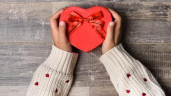 Le braccia di una ragazza che tiene in mano un regalo si San Valentino