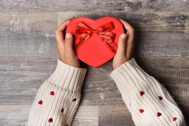 980ba69e00c708 Le braccia di una ragazza che tiene in mano un regalo si San Valentino