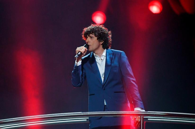 Ermal Meta, in blu, in piedi, canta al microfono su sfondo rosso