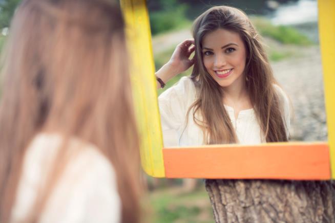 Una ragazza si specchia sorridendo