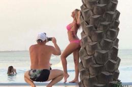 Un uomo scatta foto ad una donna in posa vicino ad una palma