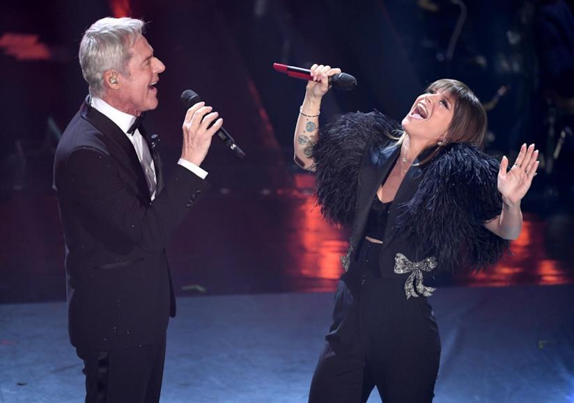 Alessandra Amoroso e Claudio Baglioni, in piedi, uno di fronte all'altro, in nero, cantano al microfono