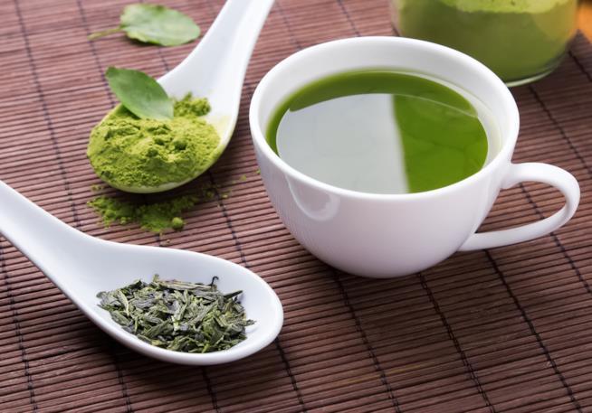 Tazza di tè verde su una tovaglietta marrone