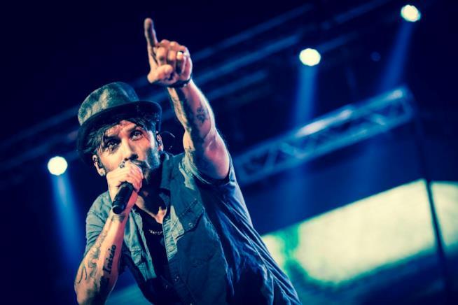 Fabrizio Moro con il cappello e il braccio sinistro alzato, nella mano destra il microfono