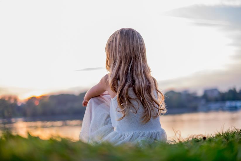 Bambina seduta su un prato guarda il lago