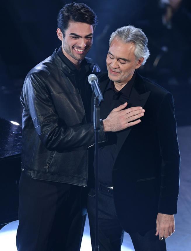 Andrea Bocelli e il figlio Matteo, in nero, in piedi, abbracciati