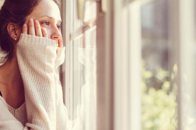 Una donna affacciata alla finestra con le mani sulle guance