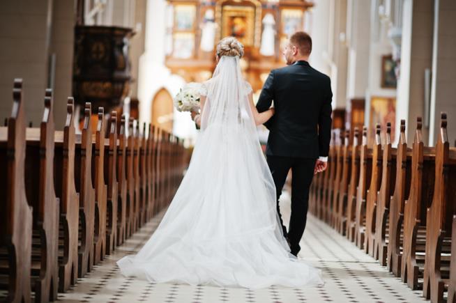 Una giovane coppia di sposi si dirige all'altare