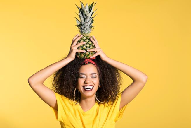 Ragazza ride con un'ananas in testa