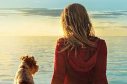 Una donna fissa l'orizzonte insieme a un cane