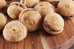 Tagliere di legno con biscottini di baci di dama al cioccolato