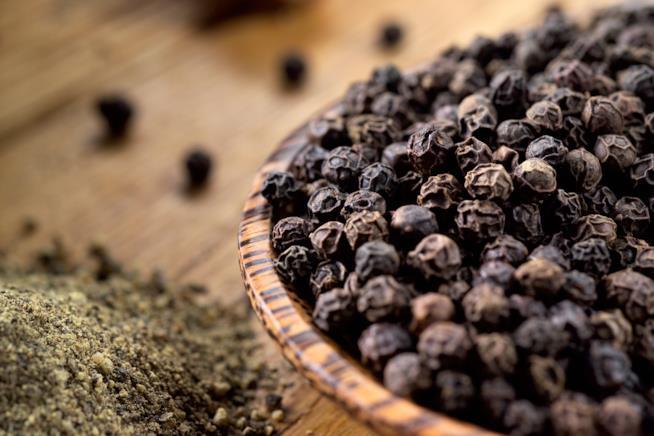una bacinella di pepe nero in grani e vicino in polvere