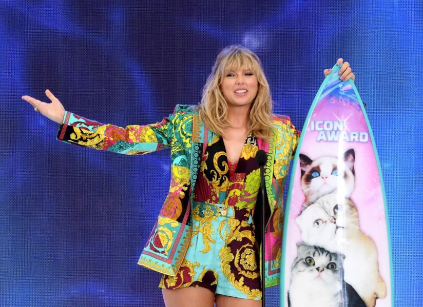 Taylor Swift in piedi, vicino a una tavola da surf