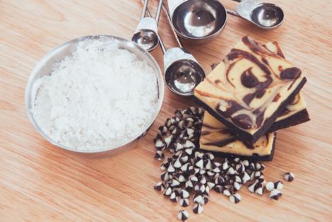 Quadrati di cheesecake con base di brownie vicino a ciotola di farina e gocce di cioccolato