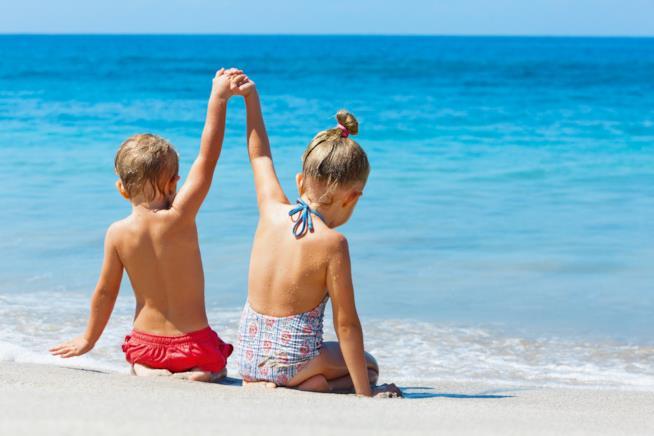Due bambini mentre si tengono la mano in riva al mare.