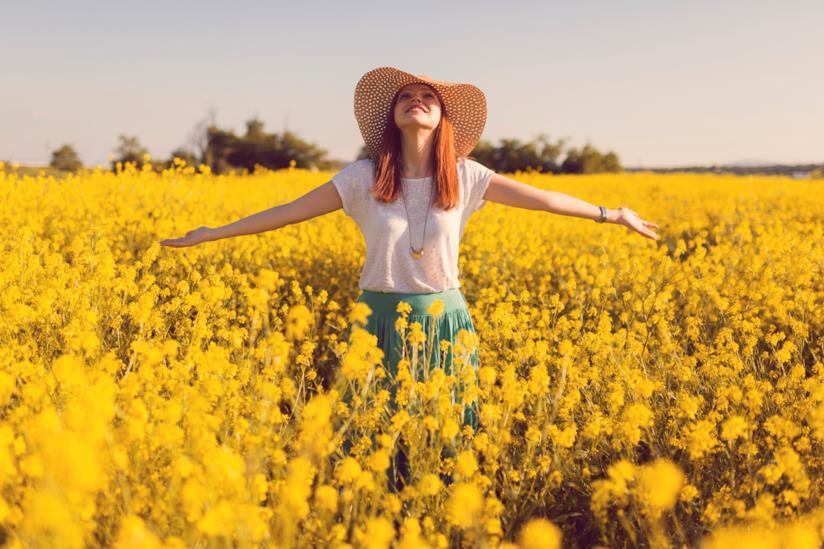 Ragazza in un campo di fiori a braccia aperte
