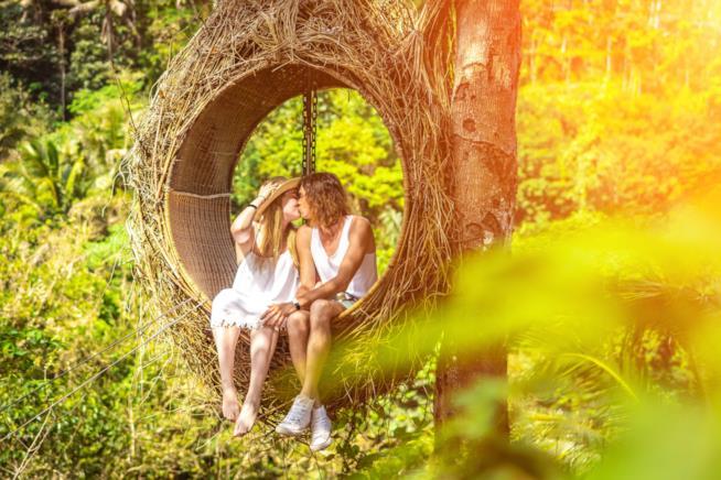 Coppia che si bacia su un'altalena in un bosco