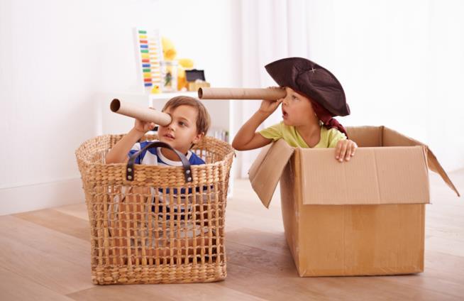 Bimbi che giocano ai pirati usando uno scatolone e un cesto come imbarcazioni