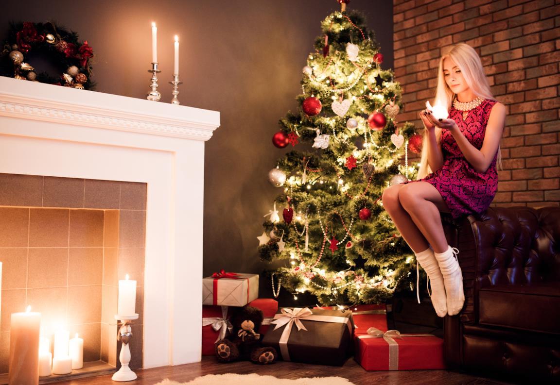 Una ragazza seduta vicino all'albero di Natale