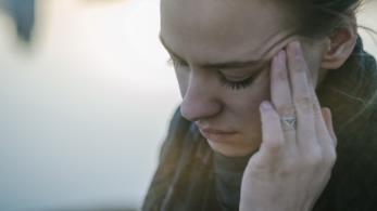 Una donna si massaggia la tempia con sofferenza