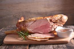 Agnello cotto al forno con rosmarino su tavolo da cucina bianco.