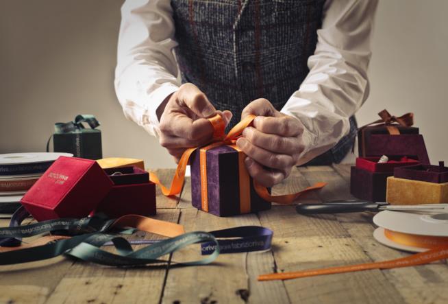 Uomo confeziona il pacchetto di Natale