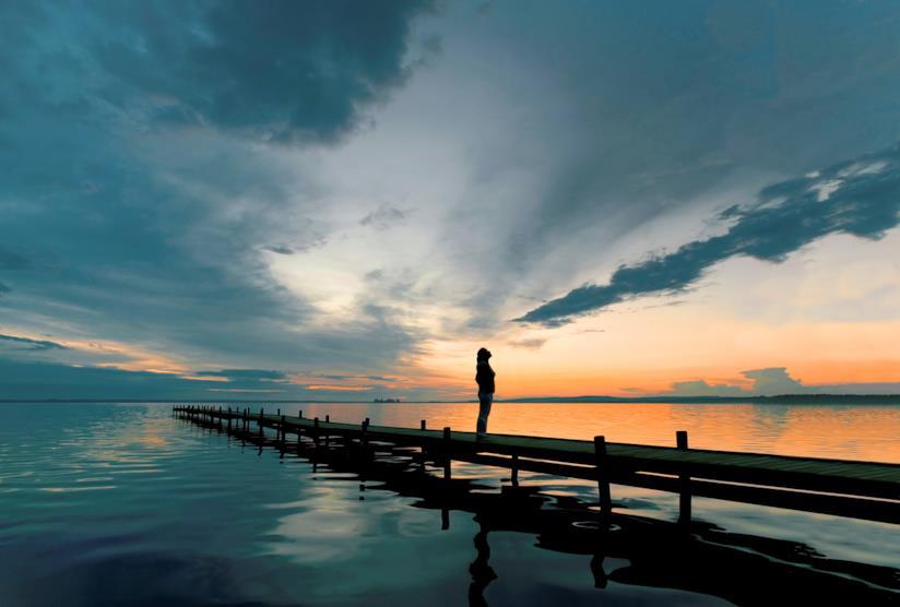 Ragazza su un pontile al tramonto
